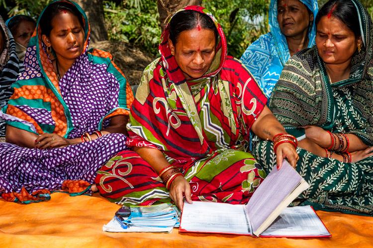 Vrouwen van Omm Sairam tonen het groepskasboek en de individuele boekjes, op de stapel links (foto: Opmeer Reports)