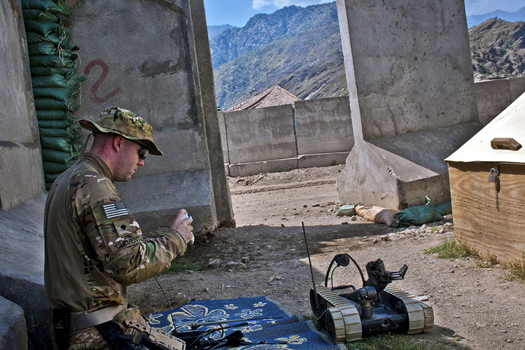 Amerikaanse soldaat leest een robot uit in Afghanistan (foto: US Army)